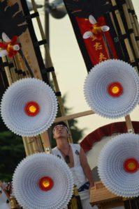 戸畑祇園大山笠競演会での大きく傾く幟山笠と台上の男
